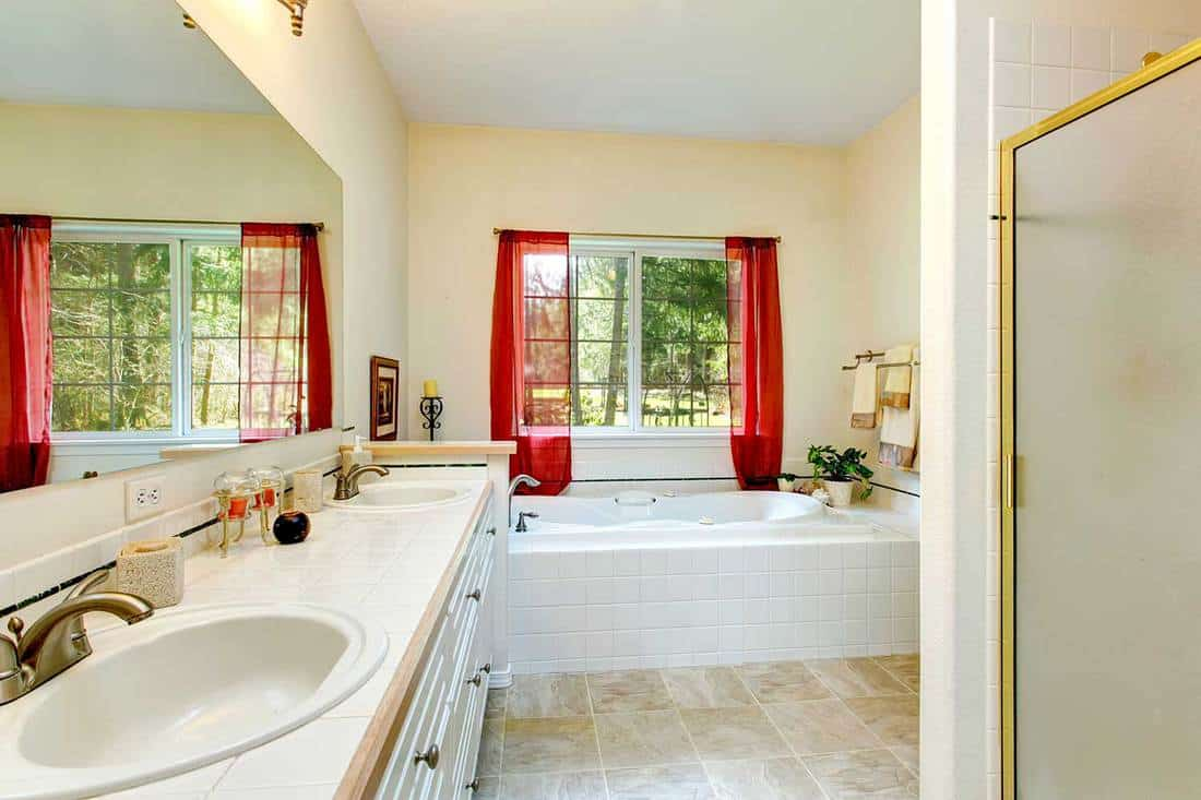 Beautiful ivory bathroom with a concrete floor and french window, white whirlpool blend perfectly with white cabinets