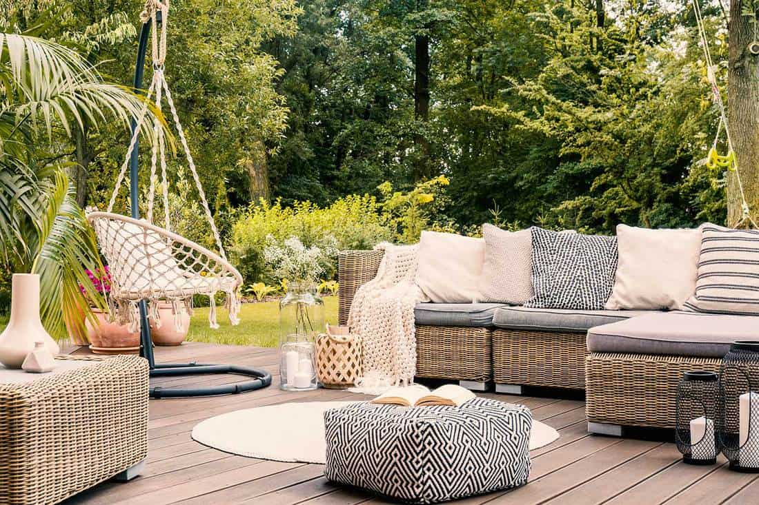 Black and white pouf in the middle of a bright garden terrace with a rattan corner sofa, hanging chair and round rug