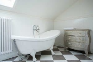 Classic bathroom with white clawfoot tub and black and white floor