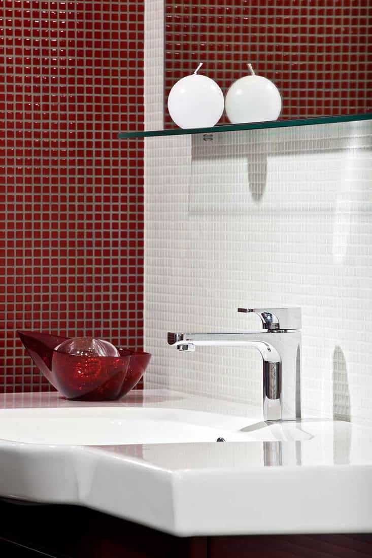 Composition with chrome faucet, mosaic tile and sink in modern luxury bathroom interior