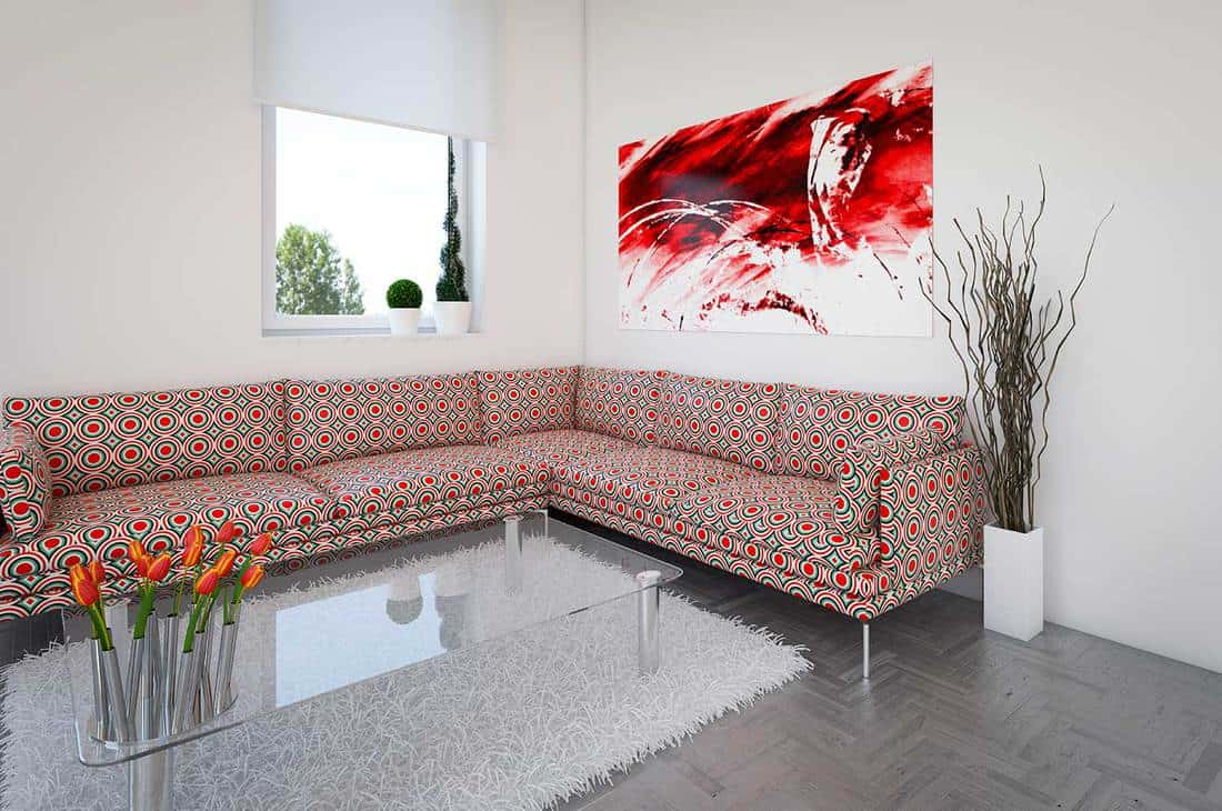 Contemporary living room with a modern corner sofa, modern coffee glass table with tulips and an abstract painting on the wall