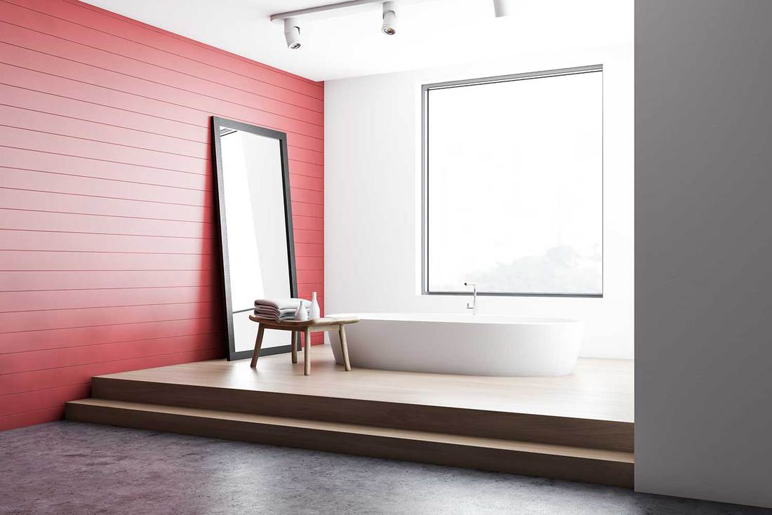 Corner of stylish bathroom with red and white walls, comfortable bathtub and vertical mirror on the floor