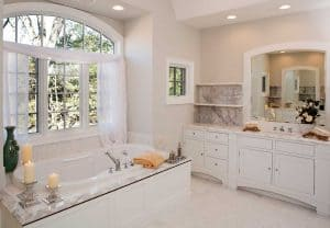 Custom white toned master bathroom with hot tub, custom cabinets and white marble surfaces