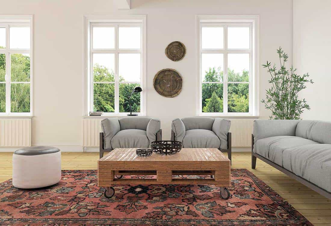 Eclectic living room interior with sofa, two armchairs and a cushion seat in a vintage modern colonial style