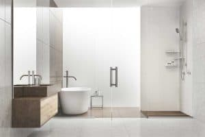 Gray and white bathroom interior with a tiled floor, a white tub, a shower and a sink