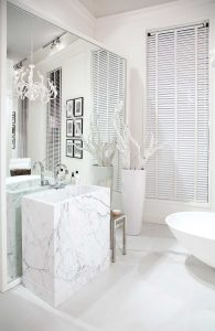 Interior of a white bathroom with large mirror and picture frames
