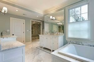 Large master bathroom in luxury home with white cabinetry
