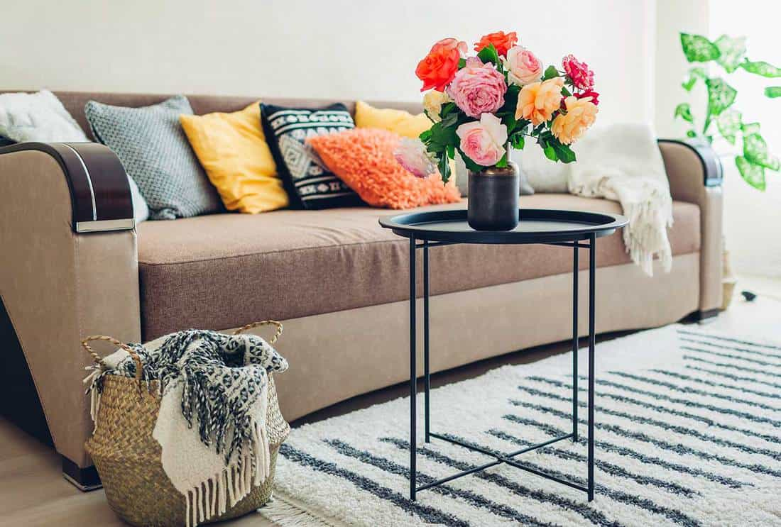 Living room decorated with bouquet of peonies, wicker basket with blanket, plants and carpet