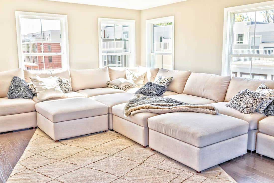 Loft interior space of modern home with staging of large beige, neutral white couches and throw rugs with pillows
