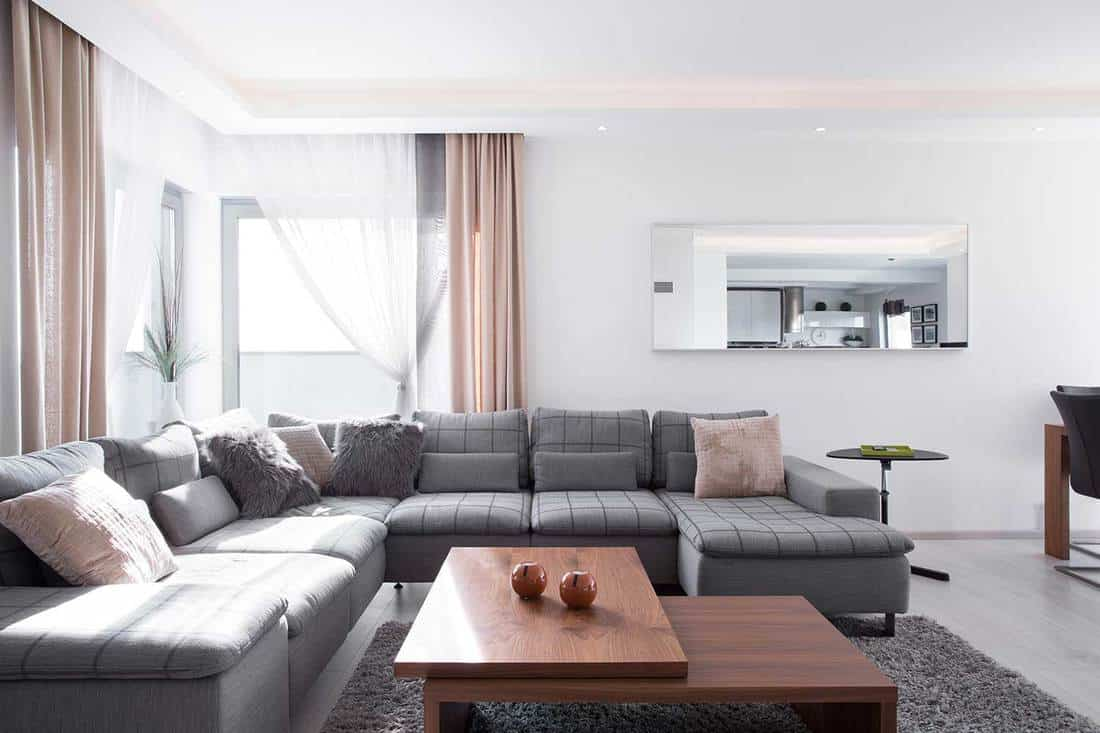 Lots of decorative cushions on comfortable corner grey sofa in a modern living room interior