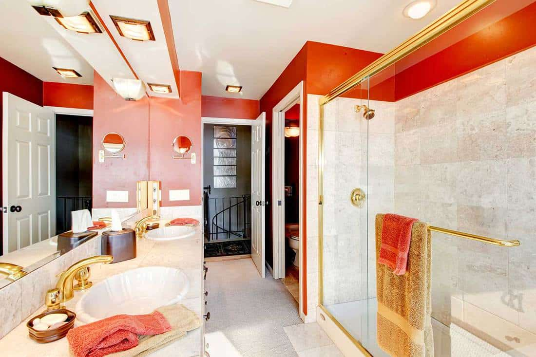 Luxury bathroom with red walls and walk-in shower with beige tiles