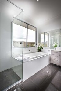 Elegant white bathroom interior with a glass shower cubicle and bath tub under a window in shades of grey and white