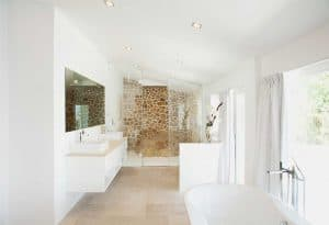 White and cream bathroom interior with two sink and bathtub