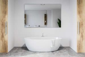 Stylish bathroom interior with white walls, concrete floor, white bathtub with large mirror hanging above it