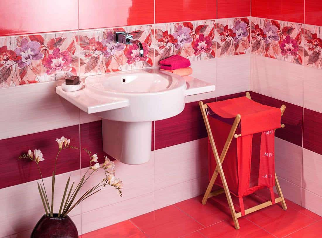 Modern bathroom with floral motif tiles and accessories in red