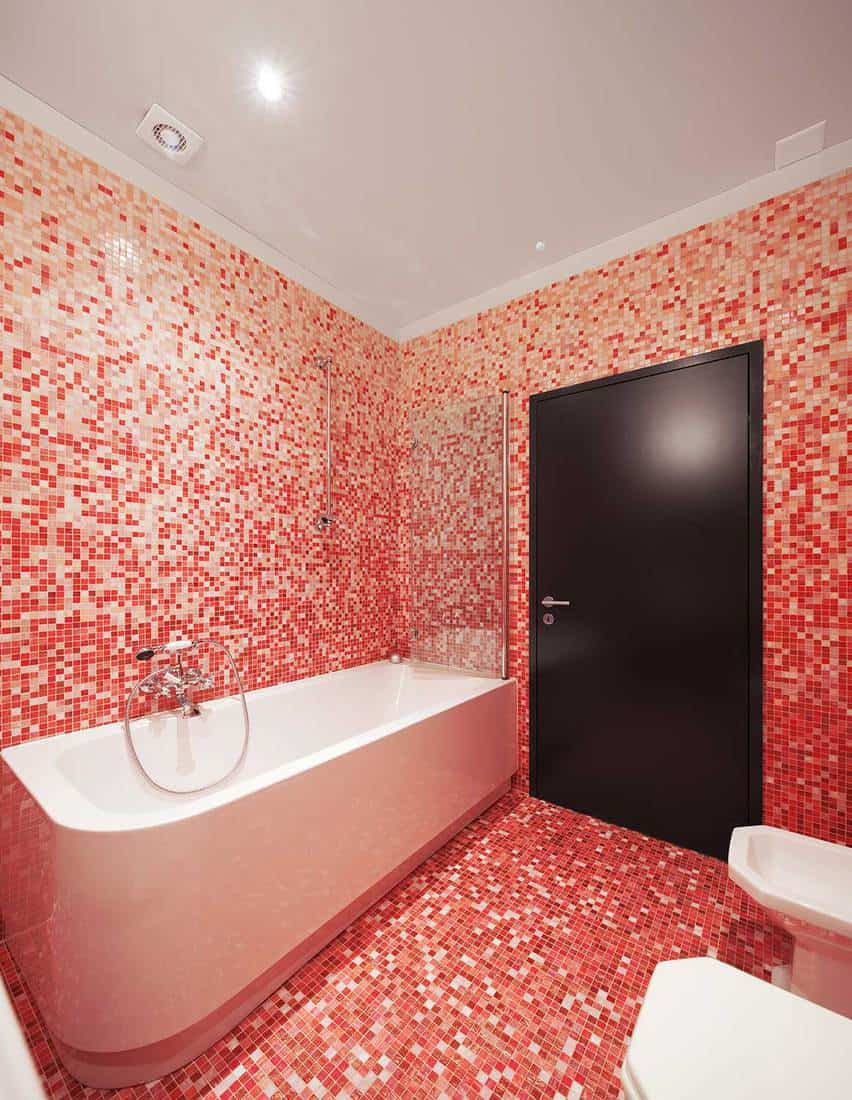 Modern bathroom with red mosaic tiles and a bathtub