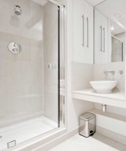 Serene bathroom design with white ceramic basin and shower cabin