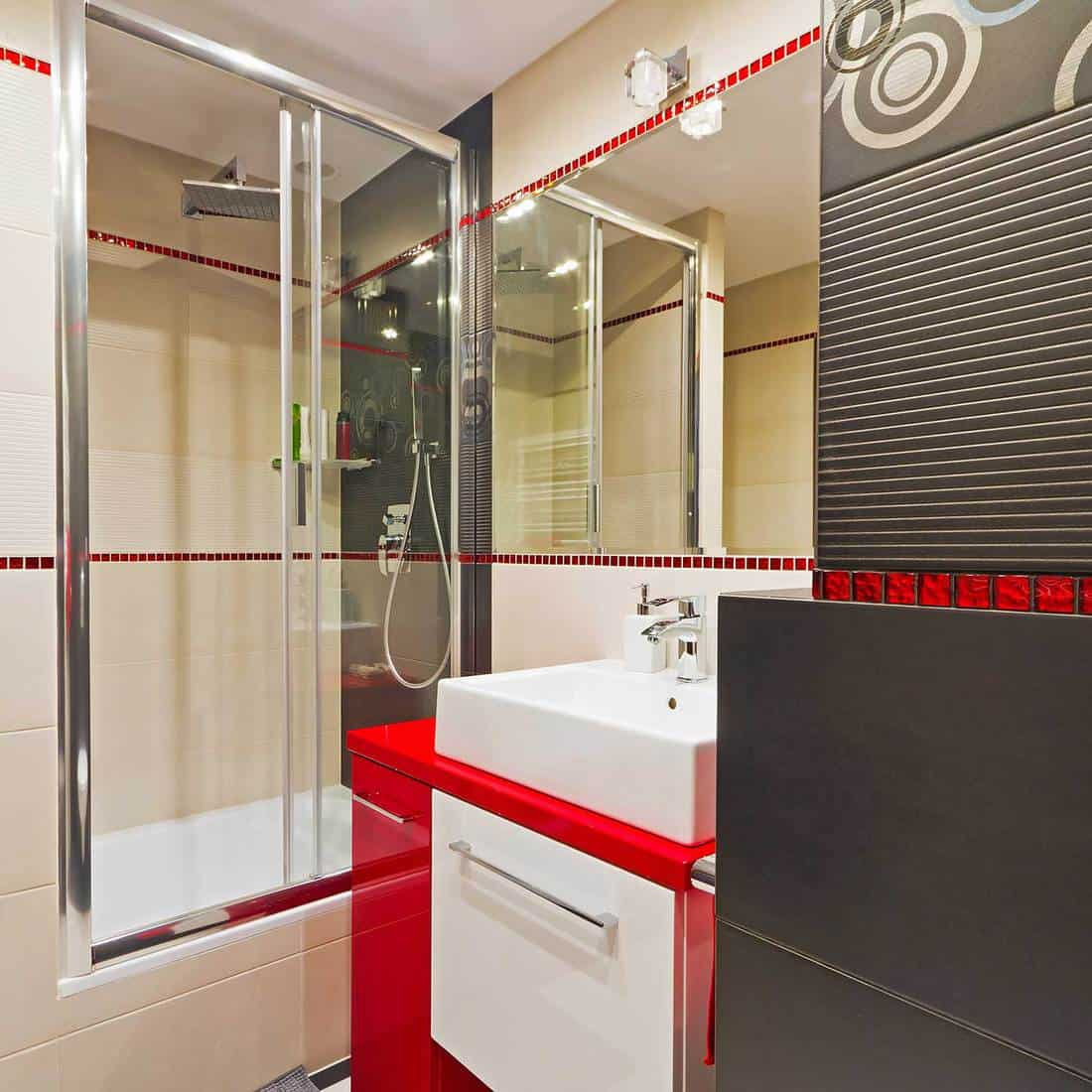 Modern black, red and white bathroom interior with shower and sink