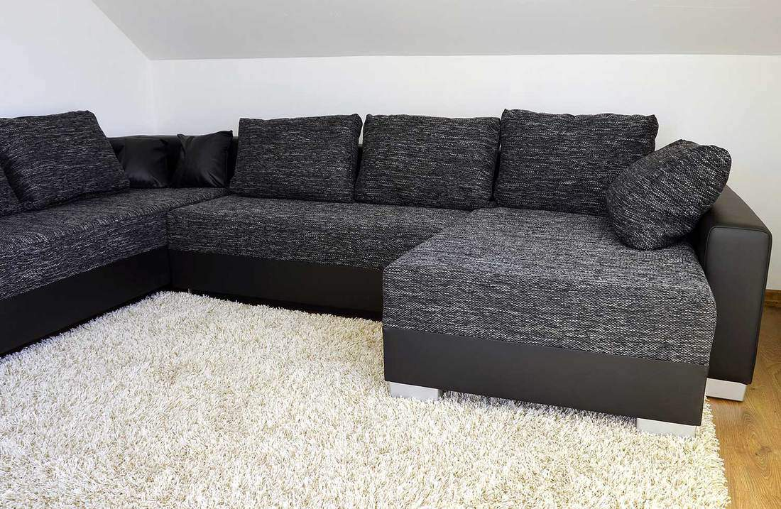 Modern black sofa and pillows on shaggy white carpet