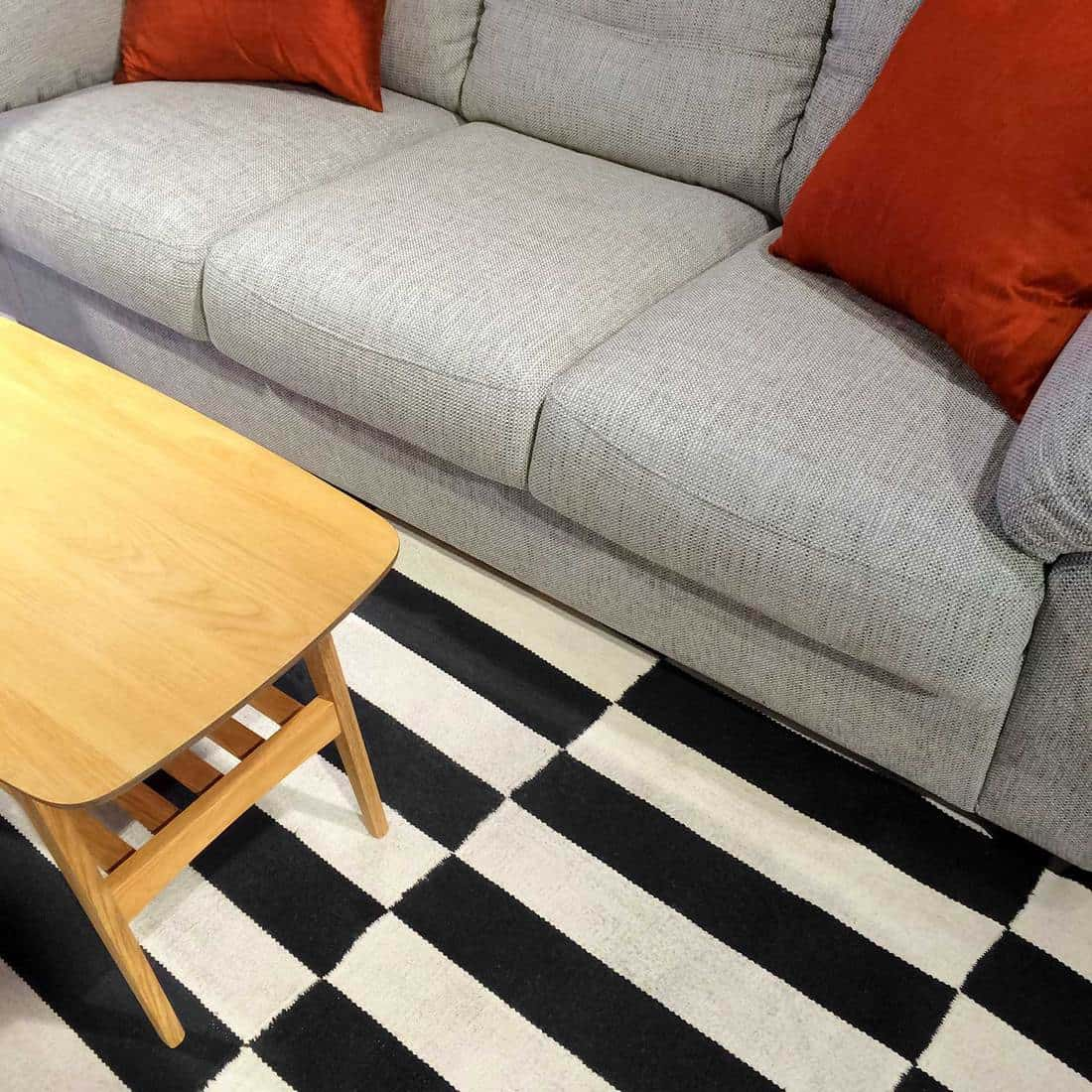 Modern grey sofa with orange cushion pillow and coffee table on striped carpet