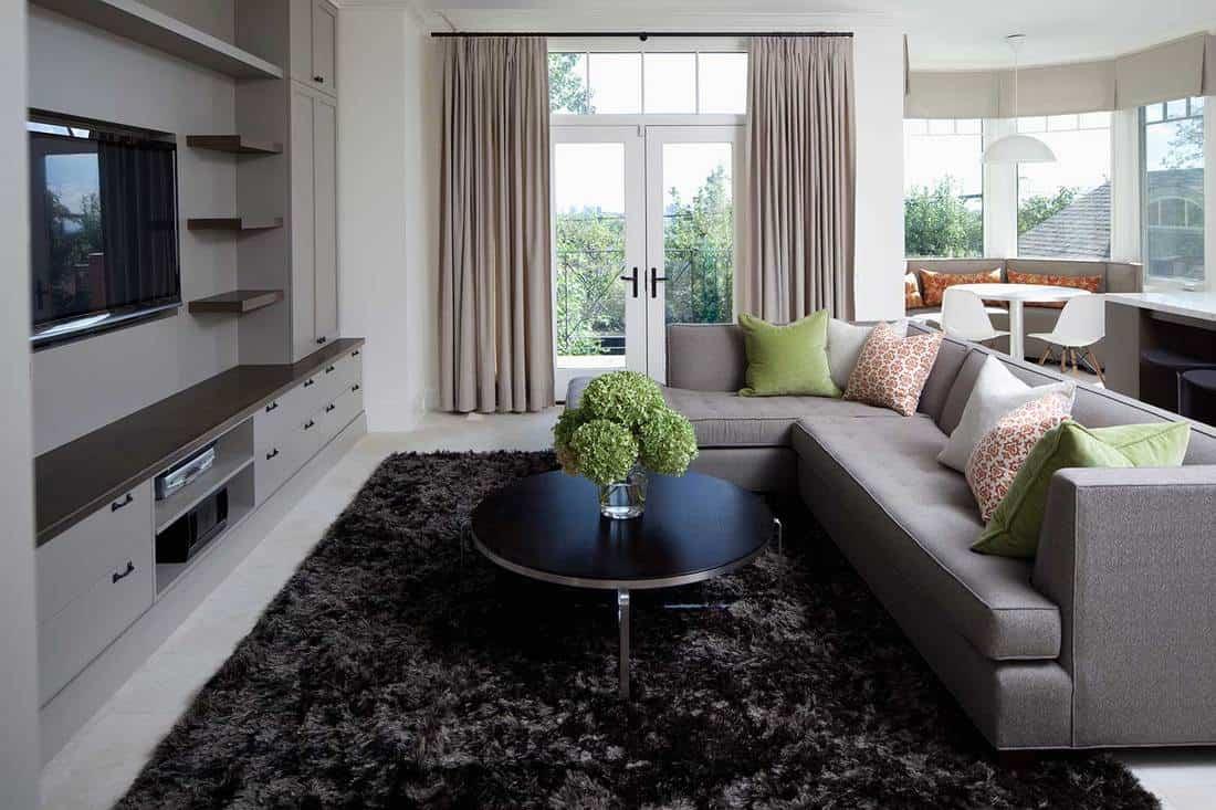 Modern home living room interior with balcony, grey sofa, dark rug and coffee table