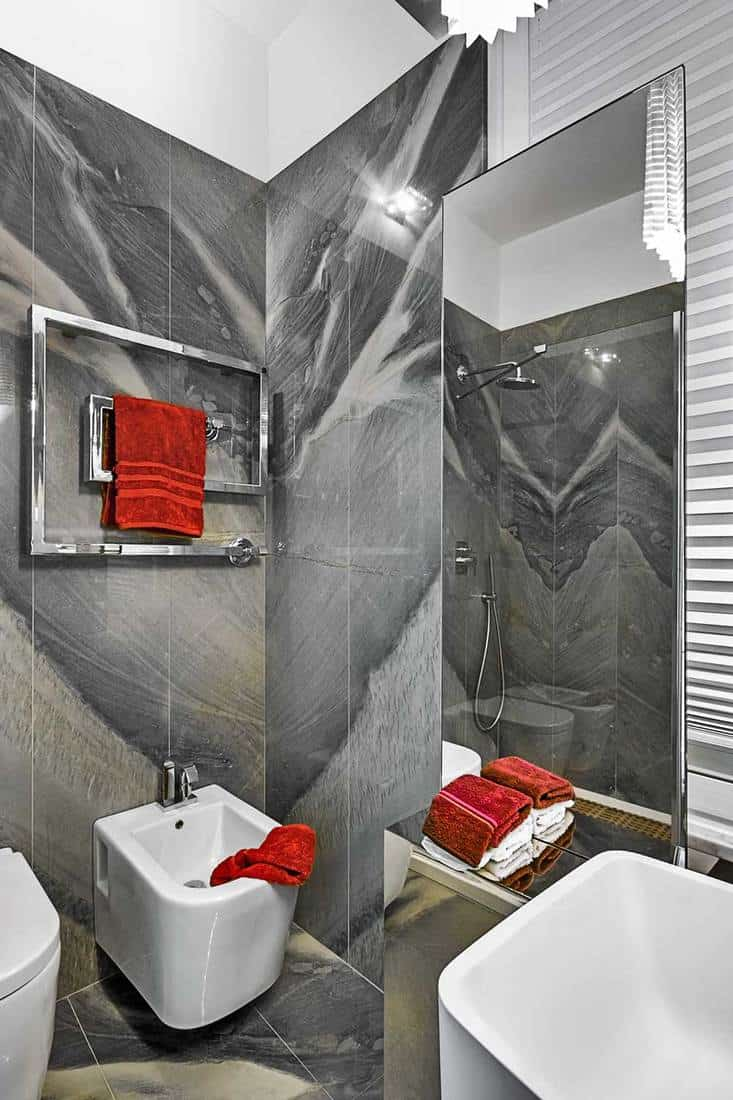 Modern little bathroom with red towels and marble grey walls