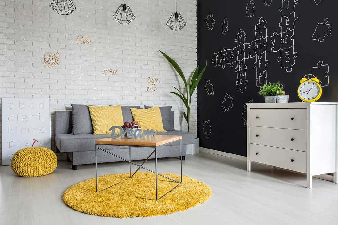 Modern living room interior with yellow and grey sofa, blackboard wall and wooden coffee table