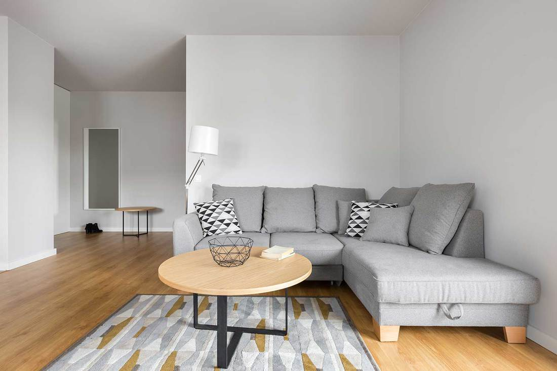 Modern living room with grey sofa, decorative pillows and small round table