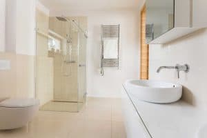 Simple white bathroom with bright tiles with glass shower, toilet and sink