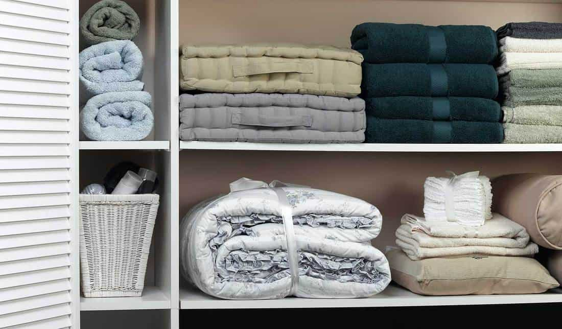 Organized linen closet with towels, blankets pillows and bed sheets