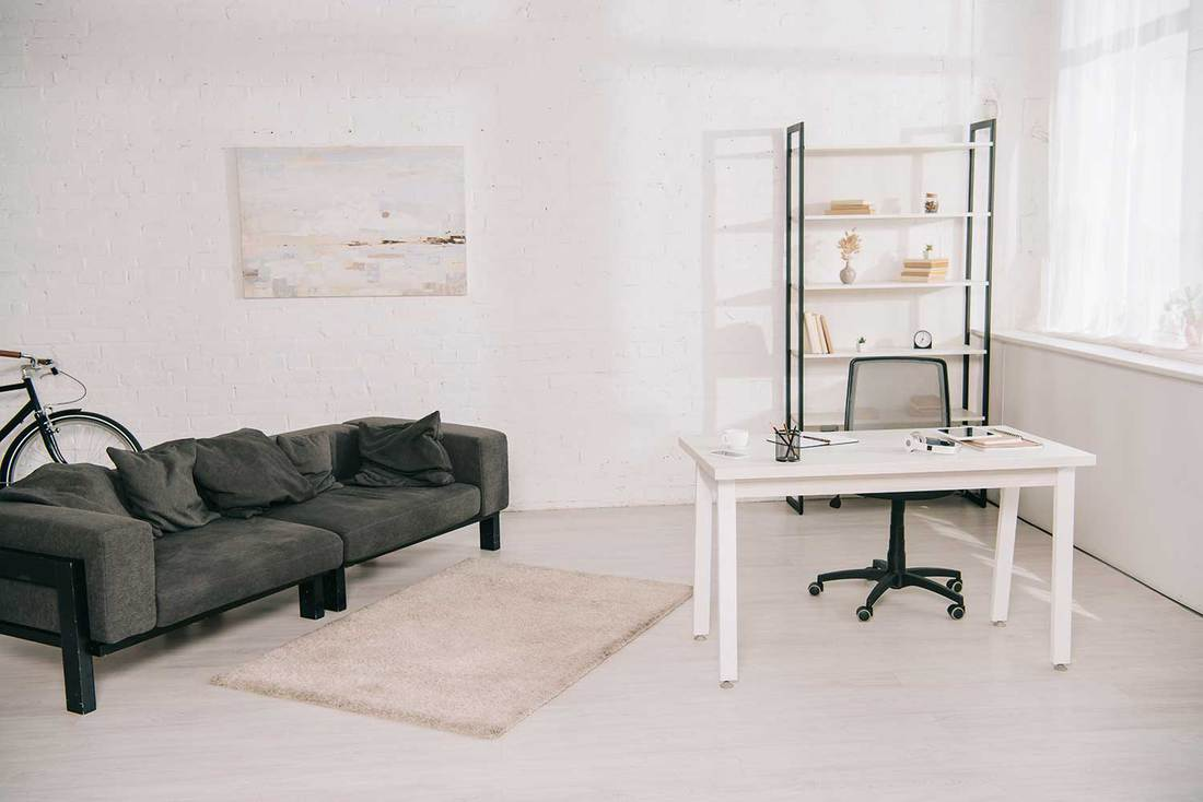 Spacious living room office with grey sofa, white table and rack with books