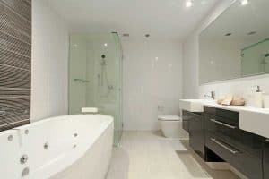 Stylish bathroom with two sinks, mirror, shower, toilet and round bathtub