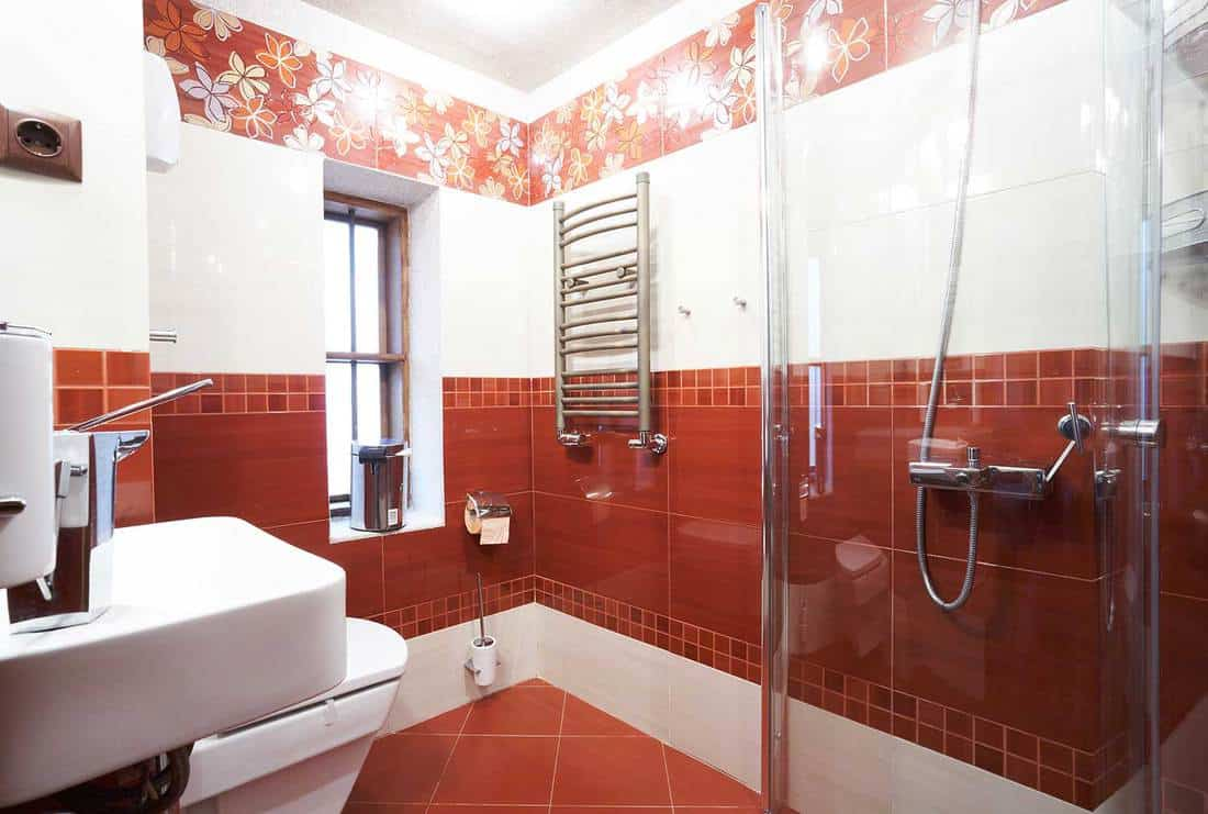 Stylish floral hotel bathroom interior with red and white tile walls