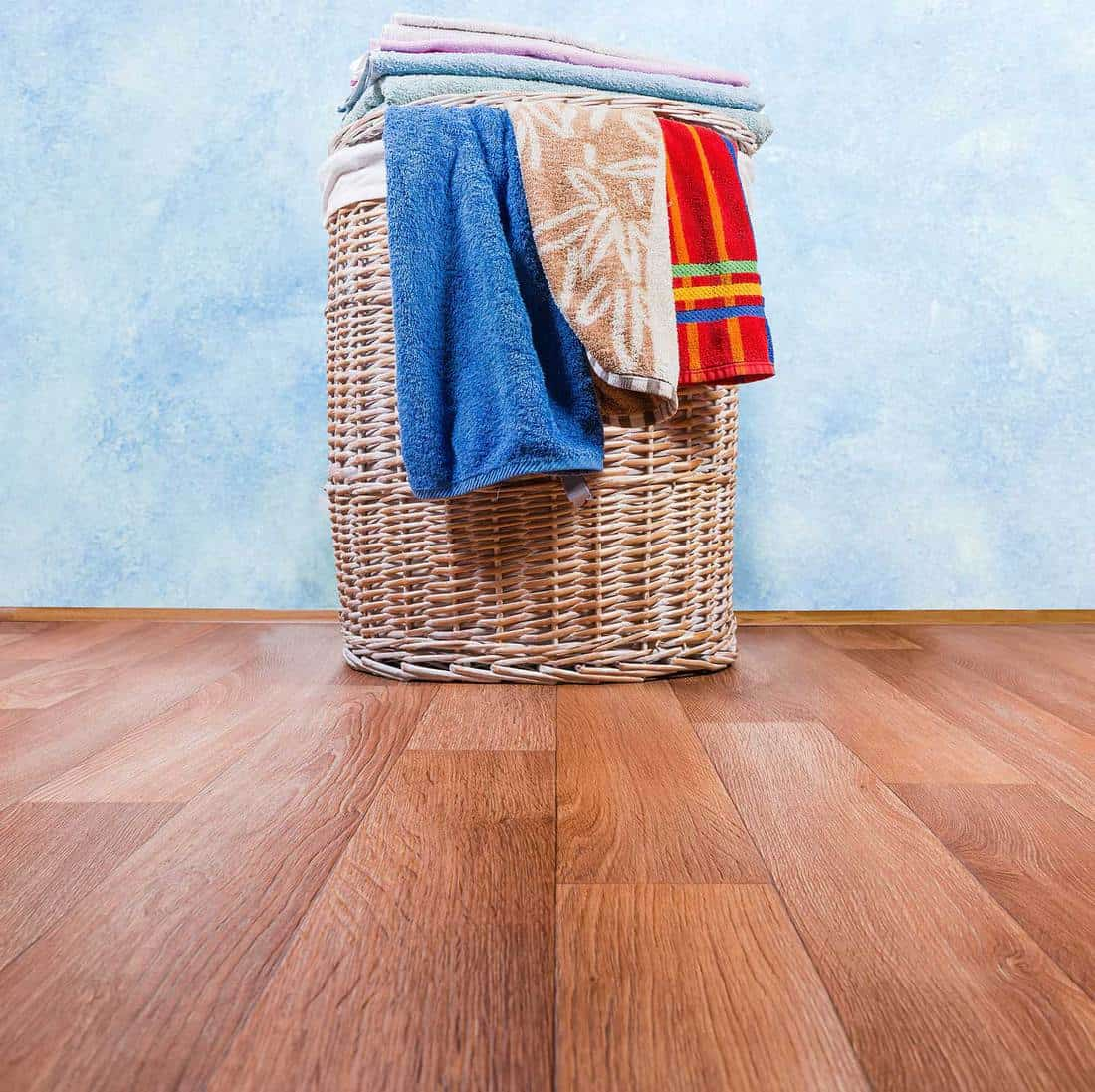 Wooden laundry hamper basket standing on the floor with towels and blankets hanging