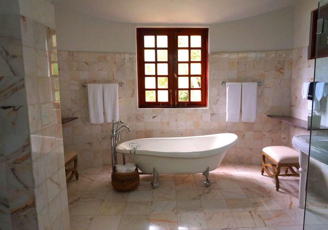White bathtub on a white tile bathroom near brown framed clear glass window