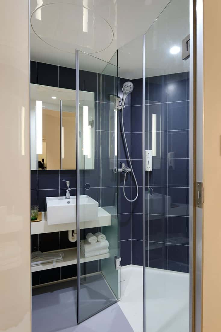 A bathroom with clear glass shower stall