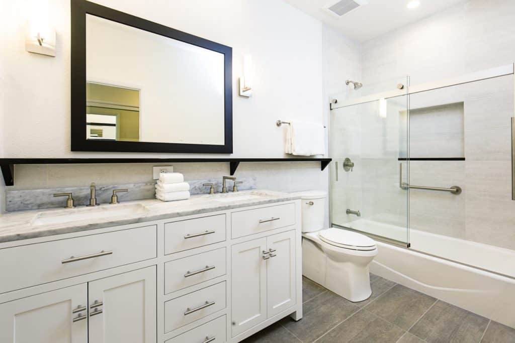 A contemporary modern bathroom featuring a bathtub with glass shower stall, toilet and his and her double sink vanity