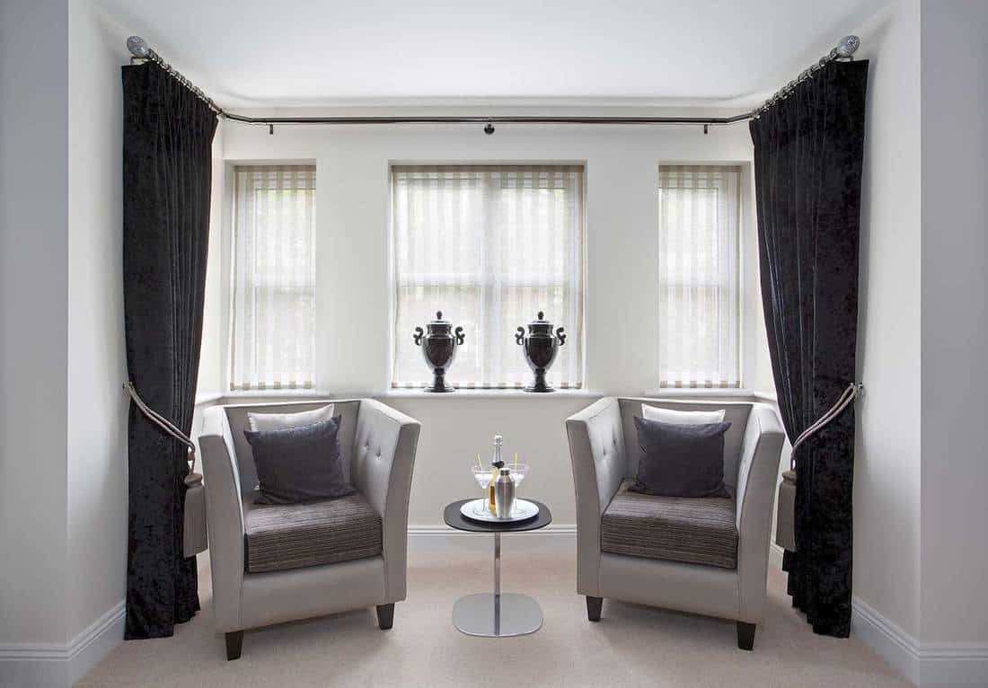 A bay window in a luxury home with two armchairs aside a small glass and chrome coffee table with a bottle of champagne, two martini glasses and a cocktail mixer