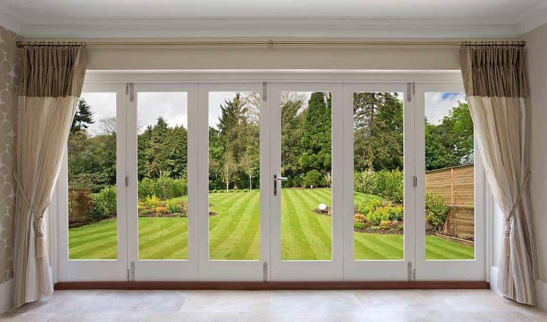 A set of concertina patio doors with silk curtains on either side and a view of a fabulous garden