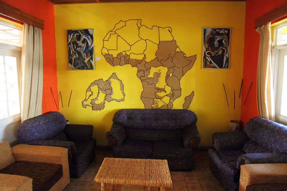 A small living room with a partly finished mural of Africa and Rwanda on the wall