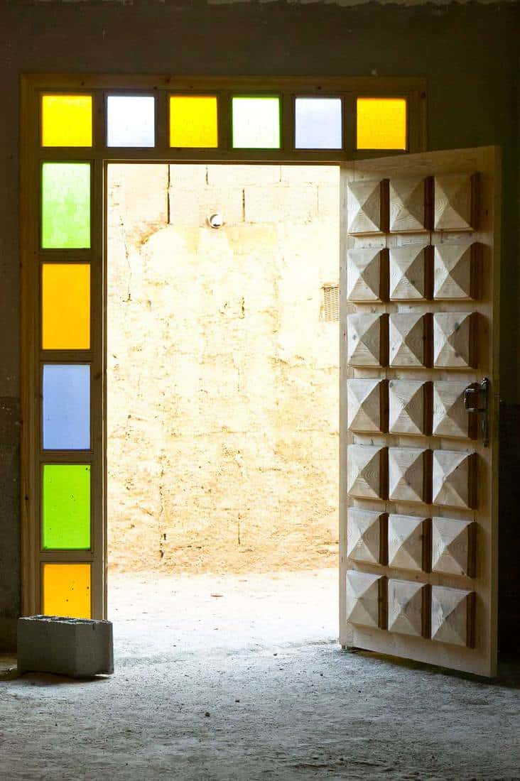 An open wooden door surrounded by stained glass