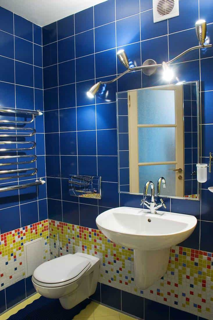 Bathroom with toilet, sink, mirror and blue wall tiles