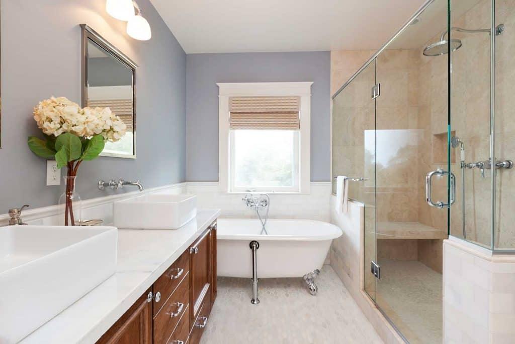 Beautiful modern house bathroom with bathtub, two ceramic wash basin and shower