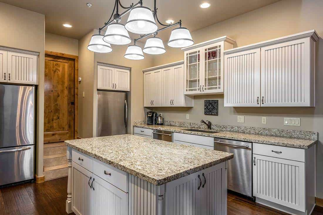 Beautiful modern kitchen with island table, hardwood floor, white cabinets and stainless steel appliances