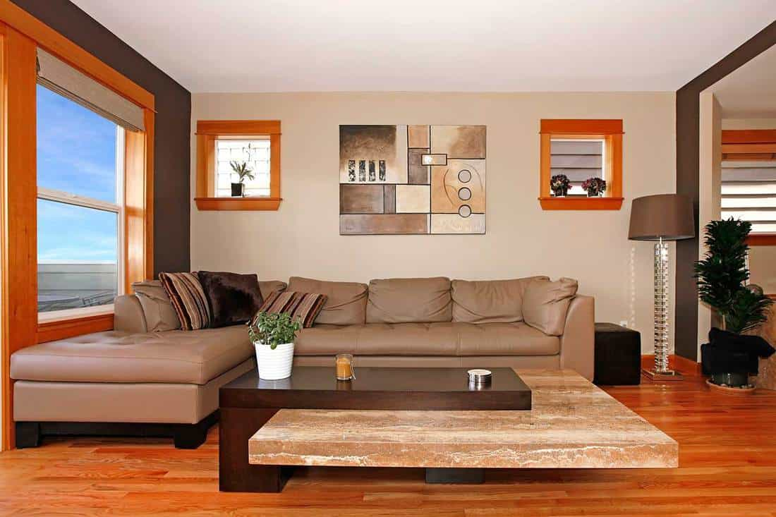Beautiful modern living room interior with brown leather sofa, wall art decor, parquet floor and glass window