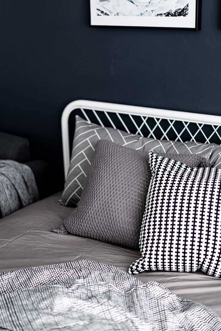 Bedroom corner setting with comfortable graphic pillows in neutral color with navy blue painted wall