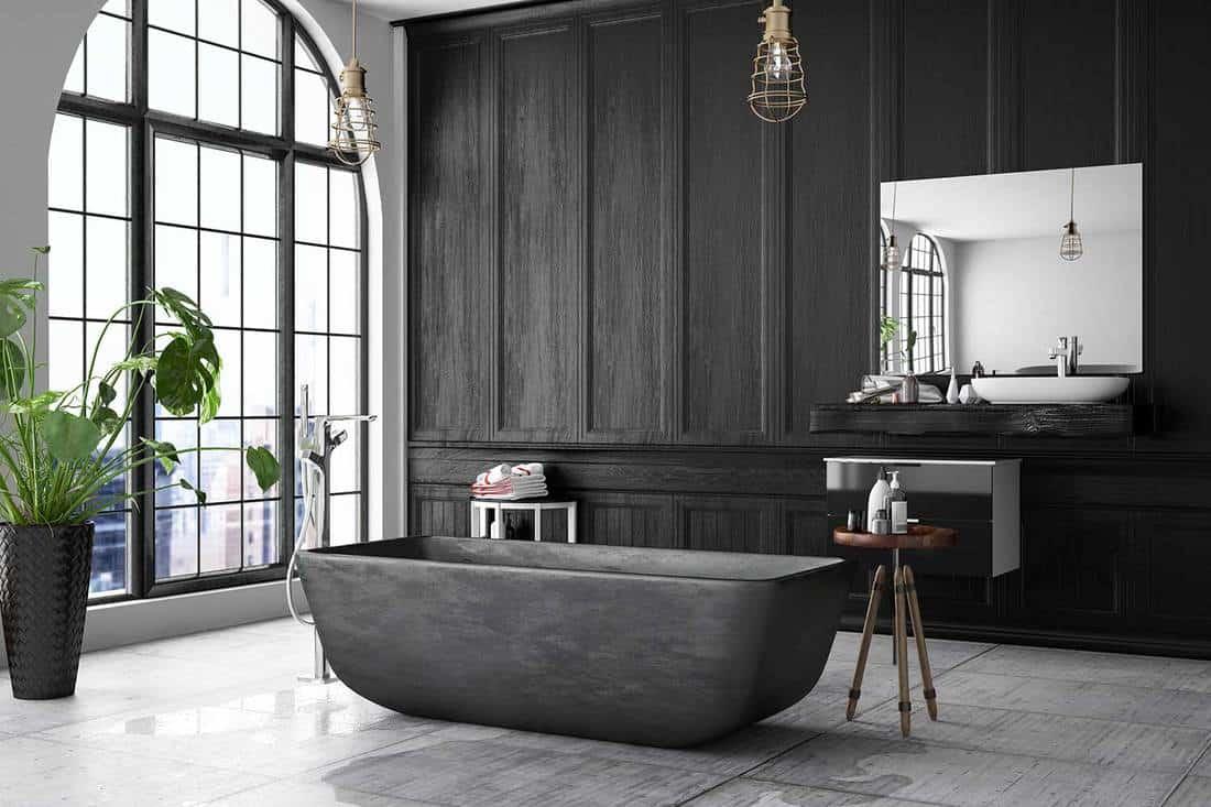 Black bathtub in modern loft interior bathroom with dark wood walls