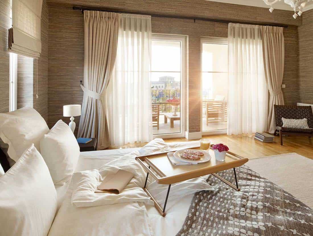 Breakfast on bed in a modern bedroom with balcony