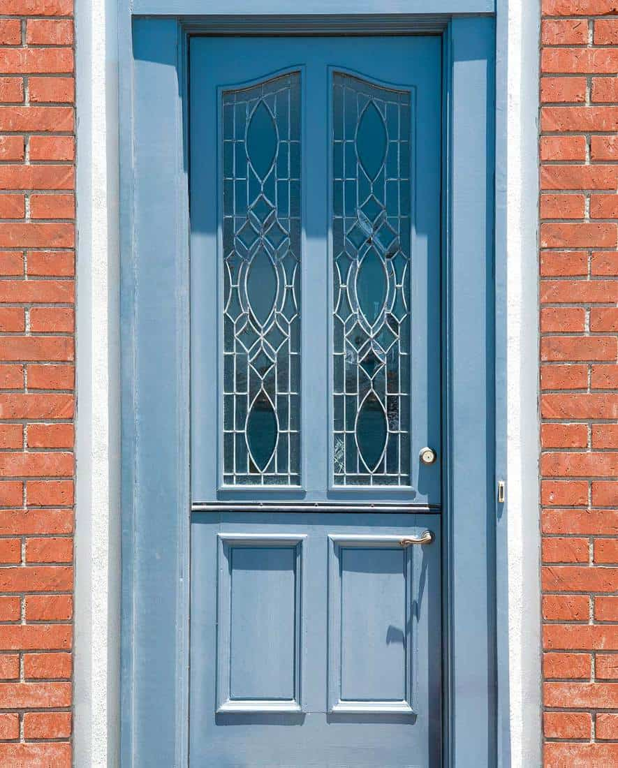 Brick entrance with blue front door with leaded glass