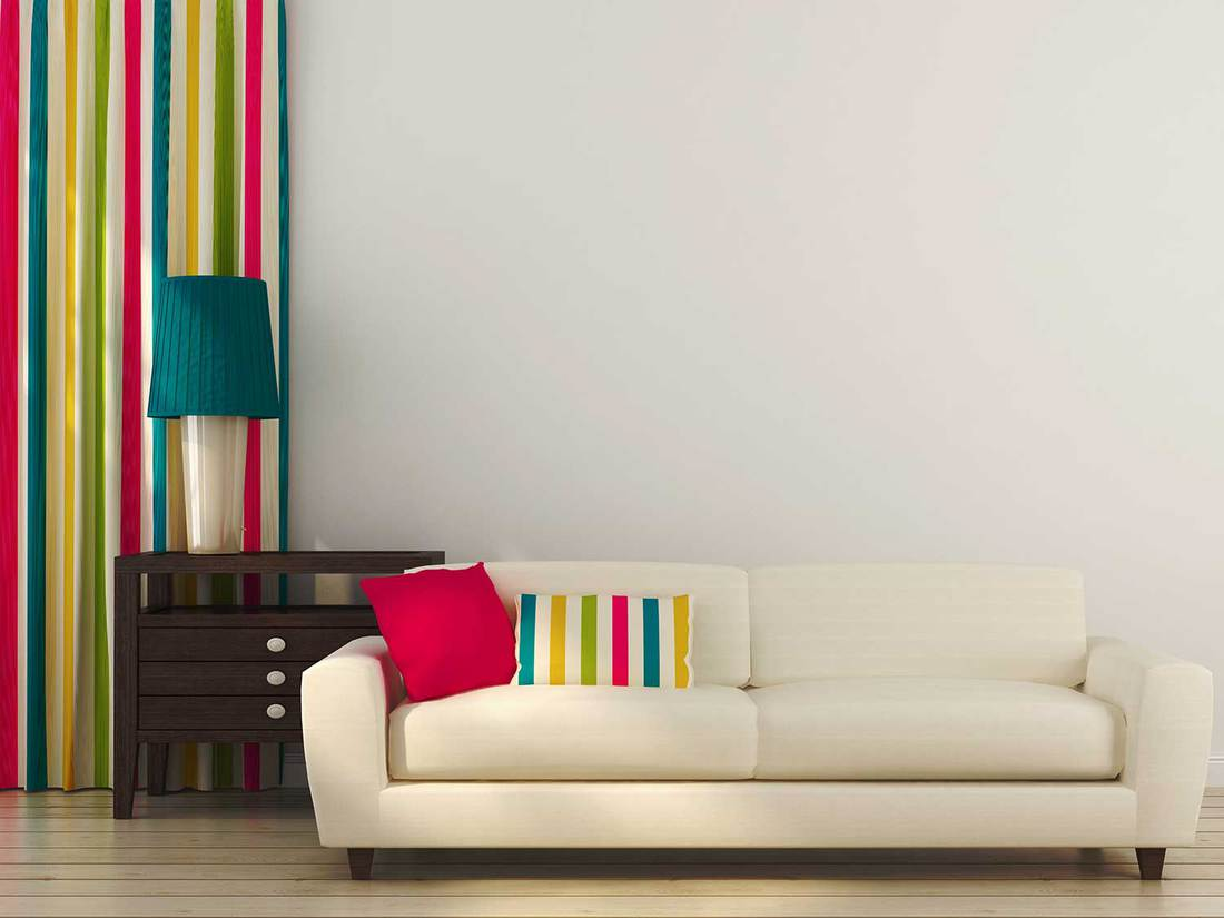 Bright living room consisting of a white sofa, colored pillows, curtains and drawer unit with table lamp